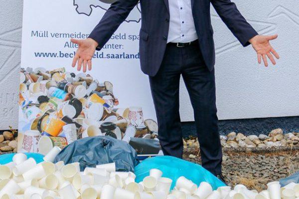 Staatssekretär Roland Krämer zeigt, wie viele 2Go-Becher pro Stunde im Saarland weggeworfen werden